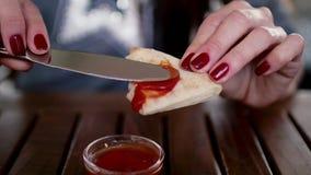 Το κορίτσι κρατά το ψωμί στα χέρια της και διαδίδει το κέτσαπ ή τη σάλτσα σε το απόθεμα βίντεο