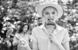 Το κορίτσι κρατά τα δίκρανα με το λουκάνικο και το αγγούρι Εναλλακτική διατροφή για τους χορτοφάγους Κρέας ή λαχανικά επιλογής αυ στοκ φωτογραφία με δικαίωμα ελεύθερης χρήσης