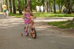 Το κορίτσι οδηγά ένα τετράτροχο ποδήλατο των παιδιών στο πάρκο στοκ φωτογραφία