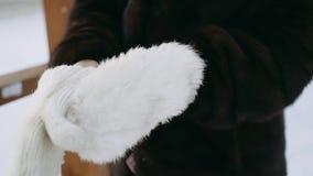 Το κορίτσι σε ένα παλτό βιζόν φορά τα άσπρα γάντια Γάντια κινηματογραφήσεων σε πρώτο πλάνο απόθεμα βίντεο