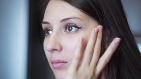 Το κορίτσι τρίβει sensually την κρέμα στο πρόσωπό σας απόθεμα βίντεο