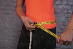 Το κορίτσι χρησιμοποιεί ένα μετρώντας φλυτζάνι για να μετρήσει την περιφέρεια του σώματος στοκ φωτογραφίες με δικαίωμα ελεύθερης χρήσης