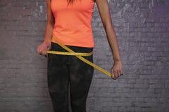 Το κορίτσι χρησιμοποιεί ένα μετρώντας φλυτζάνι για να μετρήσει την περιφέρεια του σώματος στοκ εικόνα με δικαίωμα ελεύθερης χρήσης