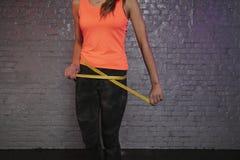 Το κορίτσι χρησιμοποιεί ένα μετρώντας φλυτζάνι για να μετρήσει την περιφέρεια του σώματος στοκ εικόνες
