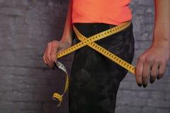 Το κορίτσι χρησιμοποιεί ένα μετρώντας φλυτζάνι για να μετρήσει την περιφέρεια του σώματος στοκ φωτογραφία με δικαίωμα ελεύθερης χρήσης