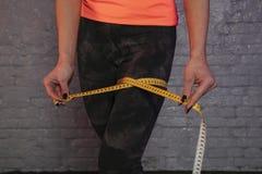 Το κορίτσι χρησιμοποιεί ένα μετρώντας φλυτζάνι για να μετρήσει την περιφέρεια του σώματος στοκ εικόνες με δικαίωμα ελεύθερης χρήσης