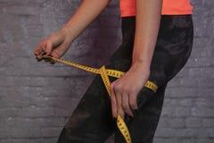 Το κορίτσι χρησιμοποιεί ένα μετρώντας φλυτζάνι για να μετρήσει την περιφέρεια του σώματος στοκ φωτογραφίες