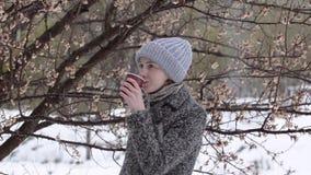 Το κορίτσι πίνει τον καφέ από ένα δέντρο ανθών Υγρό χιόνι φιλμ μικρού μήκους