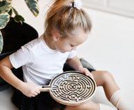 Το κορίτσι παιδιών στην άσπρη μπλούζα και τη μαύρη φούστα παίζει το εκπαιδευτικό παιχνίδι interestedly με τον ξύλινο λαβύρινθο στοκ εικόνα με δικαίωμα ελεύθερης χρήσης