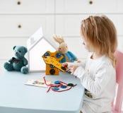 Το κορίτσι παιδιών παίζει το εκπαιδευτικό παιχνίδι interestedly με την ξύλινη ζωηρόχρωμη μπλούζα παιχνιδιών με τα κουμπιά και τις στοκ φωτογραφία με δικαίωμα ελεύθερης χρήσης