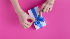 Το κορίτσι που κρατά ένα όμορφο παρόν στα χέρια, γυναίκες με το κιβώτιο δώρων με μια δεμένη μπλε κορδέλλα υποκύπτει στα χέρια σε  στοκ εικόνες με δικαίωμα ελεύθερης χρήσης