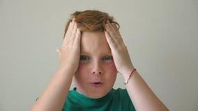 Το λατρευτό αγόρι εξετάζει τη κάμερα με τις συγκινήσεις και τα συναισθήματα στο πρόσωπο Νέοι όμορφοι συμπλέκτες παιδιών το κεφάλι απόθεμα βίντεο