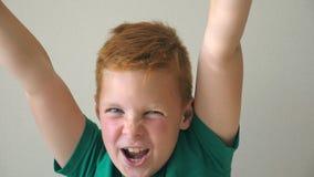 Το λατρευτό όμορφο αγόρι που εξετάζει τη κάμερα και που αυξάνει δίνει το επίτευγμα εσωτερικό Ευτυχής νεαρός με το θετικό απόθεμα βίντεο