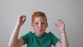 Το λατρευτό όμορφο κοκκινομάλλες αγόρι με τις φακίδες που εξετάζει τη κάμερα και αυξάνει τα χέρια το επίτευγμα μέσα απόθεμα βίντεο