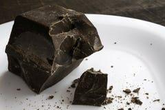 Το μεγάλο τεμαχισμένο κομμάτι της σοκολάτας σε ένα άσπρο κεραμικό πιάτο στέκεται σε έναν καφετή ξύλινο πίνακα στοκ εικόνα με δικαίωμα ελεύθερης χρήσης