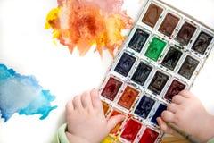 το μικρό κορίτσι με το φωτεινό πολύχρωμο watercolor χρωμάτων στα μικρά χέρια Λεκές στο άσπρο υπόβαθρο στοκ φωτογραφία