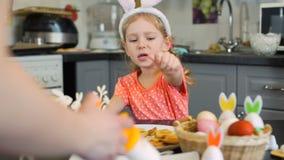 Το μικρό κορίτσι προσέχει πώς μητέρα που διακοσμεί τα μπισκότα απόθεμα βίντεο