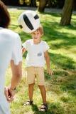 Το μικρό παιδί θερινού χρόνου που ντύνεται στην άσπρη μπλούζα εξετάζει προς τα εμπρός τη σφαίρα ποδοσφαίρου που πετά μπροστά από  στοκ φωτογραφία