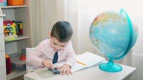 Το μικρό παιδί μετρά την αποταμίευσή του σε έναν υπολογιστή απόθεμα βίντεο