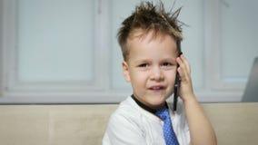 Το μικρό παιδί με ένα αναστατωμένο hairdo σε ένα άσπρο πουκάμισο και έναν μπλε δεσμό μιλά για κάτι τη διασκέδαση σε ένα τηλέφωνο  απόθεμα βίντεο