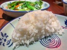 Το μισό κύπελλο μείωσε το σαφές άσπρο ρύζι σε ένα ασιατικό πιάτο στοκ εικόνες