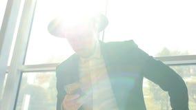 Το μοντέρνο καυκάσιο άτομο στο μαύρα κοστούμι και το καπέλο κρατά το τηλέφωνο στο χέρι και τις διαβασμένες πληροφορίες του ενώ όν απόθεμα βίντεο