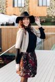 Το μοντέρνο κορίτσι που ντύνεται σε ένα μαύρο turtleneck, ένα μπεζ ακρωτήριο, μια μοντέρνα κοντά φούστα και ένα μαύρο καπέλο με τ στοκ φωτογραφία