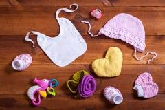 Το μωρό ντύνει τα εξαρτήματα καθορισμένα, το ρόδινο πλεκτό ιματισμό βαμβακιού, τα παιχνίδια και τον τον ετερόφθαλμο γάδο παιδιών  στοκ φωτογραφία