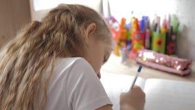 Το νέο κορίτσι κάνει την εργασία του στον πίνακα κάτω από το φως ενός λαμπτήρα δημιουργικό χόμπι λίγης πριγκήπισσας τρόπος ζωής απόθεμα βίντεο