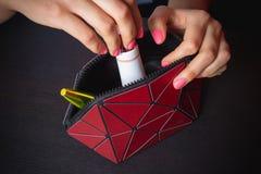 το νέο κορίτσι παίρνει την κρέμα από την τσάντα makeup της στοκ εικόνα