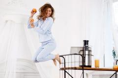 Το νέο κορίτσι brunette που ντύνεται στα ανοικτό μπλε άλματα πυτζαμών με τα πορτοκάλια σε την παραδίδει το ελαφρύ δωμάτιο δίπλα στοκ φωτογραφίες με δικαίωμα ελεύθερης χρήσης