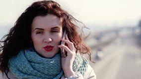 Το νέο brunette μιλά στο τηλέφωνο στεμένος στη γέφυρα Οδηγώντας αυτοκίνητα στο υπόβαθρο φιλμ μικρού μήκους
