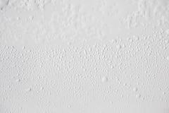 Το νερό μειώνεται κοντά επάνω στο λευκό πίνακα στοκ φωτογραφία