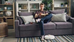 Το ξένοιαστο πρόσωπο διαβάζει το βιβλίο, πίνοντας τη συνεδρίαση τσαγιού στον καναπέ στο διαμέρισμα ενώ η ρομποτική ηλεκτρική σκού απόθεμα βίντεο