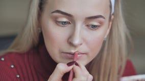 Το ξανθό κορίτσι εφαρμόζει το κραγιόν με το καλλυντικό μολύβι στα χείλια φιλμ μικρού μήκους