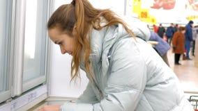 Το ξανθό κορίτσι παίρνει το φραγμό προϊόντων από την περίπτωση παραθύρων ψυγείων φιλμ μικρού μήκους