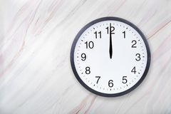 Το ρολόι τοίχων στη μαρμάρινη σύσταση παρουσιάζει δώδεκα η ώρα Το ρολόι γραφείων παρουσιάζει τη μεσημβρία ή μεσάνυχτα στοκ φωτογραφία