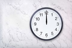 Το ρολόι τοίχων παρουσιάζει δώδεκα η ώρα στην άσπρη μαρμάρινη σύσταση Το ρολόι γραφείων παρουσιάζει τη μεσημβρία ή μεσάνυχτα στοκ εικόνες με δικαίωμα ελεύθερης χρήσης
