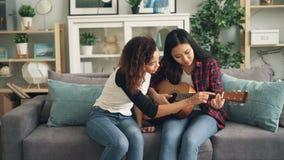 Το όμορφο ασιατικό κορίτσι στον περιστασιακό ιματισμό μαθαίνει να παίζει την κιθάρα ενώ η νέα κυρία φίλων αφροαμερικάνων της είνα απόθεμα βίντεο