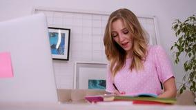 Το όμορφο ελκυστικό κορίτσι με τα ξανθά μαλλιά της ευρωπαϊκής εμφάνισης σε μια ρόδινη μπλούζα εργάζεται σε ένα lap-top σε έναν φω φιλμ μικρού μήκους