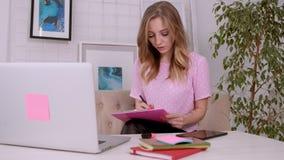 Το όμορφο ελκυστικό κορίτσι με τα ξανθά μαλλιά της ευρωπαϊκής εμφάνισης σε μια ρόδινη μπλούζα εργάζεται σε ένα lap-top σε έναν φω απόθεμα βίντεο