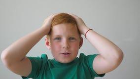 Το όμορφο κοκκινομάλλες αγόρι με τις φακίδες που εξετάζει τη κάμερα και αυξάνει τα χέρια το επίτευγμα μέσα Πορτρέτο απόθεμα βίντεο