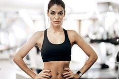Το όμορφο λεπτό κορίτσι που ντύνεται μαύρο sportswear στέκεται στη γυμναστική και κρατά τα χέρια της στη μέση της στοκ εικόνες