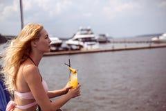 Το όμορφο νέο ξανθό κορίτσι στο ρόδινο μπικίνι πίνει το κοκτέιλ με το χυμό στο θέρετρο στοκ φωτογραφίες με δικαίωμα ελεύθερης χρήσης