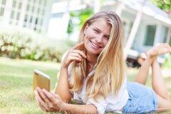 Το όμορφο ξανθό κορίτσι, σε έναν θερινό πράσινο χορτοτάπητα, με ένα smartphone στα χέρια της απολαμβάνει τον ήλιο στοκ φωτογραφίες