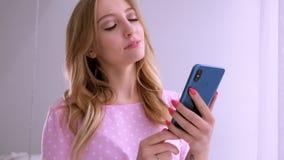 Το όμορφο ξανθό κορίτσι σε μια ρόδινη μπλούζα της ευρωπαϊκής εμφάνισης επικοινωνεί τηλεφωνικώς στο παράθυρο στο φωτεινό απόθεμα βίντεο