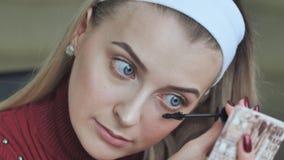 Το όμορφο ξανθό κορίτσι χρωματίζει τα eyelashes της απόθεμα βίντεο