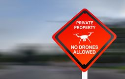 Το σημάδι ιδιωτικών ιδιοκτησιών, κανένας κηφήνας επέτρεψε - κόκκινο προειδοποιητικό σημάδι σε μια οδό, με την επιτάχυνση του θολω στοκ εικόνα