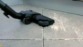 Το σκούπισμα με ηλεκτρική σκούπα βρώμικο το πάτωμα κουζινών με το γκρίζο κεραμίδι και τις νιφάδες καλαμποκιού και το αλεύρι διασκ απόθεμα βίντεο
