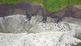 Το συναρπαστικό βίντεο άνωθεν μιας τρομερής παραλίας με τη μαύρη άμμο που κρύβεται βαθιά στη ζούγκλα, ωκεάνια κύματα πλένει το Μα φιλμ μικρού μήκους